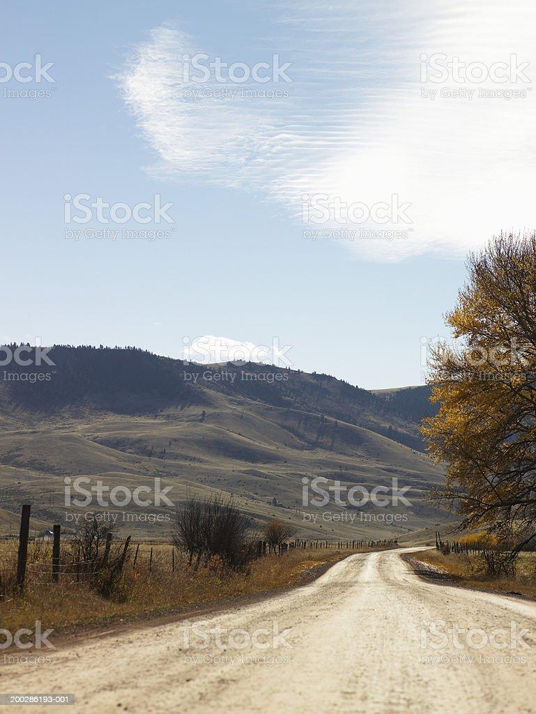 USA, Montana, Bozeman, dirt road beside hill, autumn stock photo