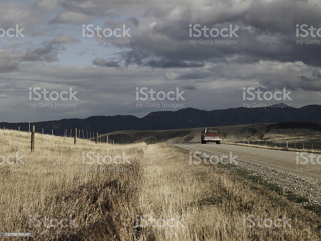 USA, Montana, Bozeman, person driving SUV down dirt road, rear view stock photo