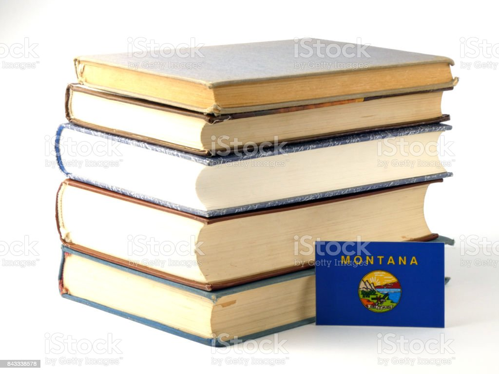 Montana flag with pile of books isolated on white background stock photo