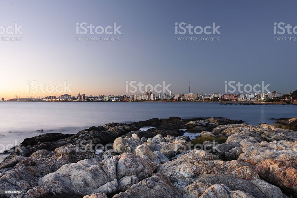 Montevideo city scape with rocks at the coast at dusk stock photo