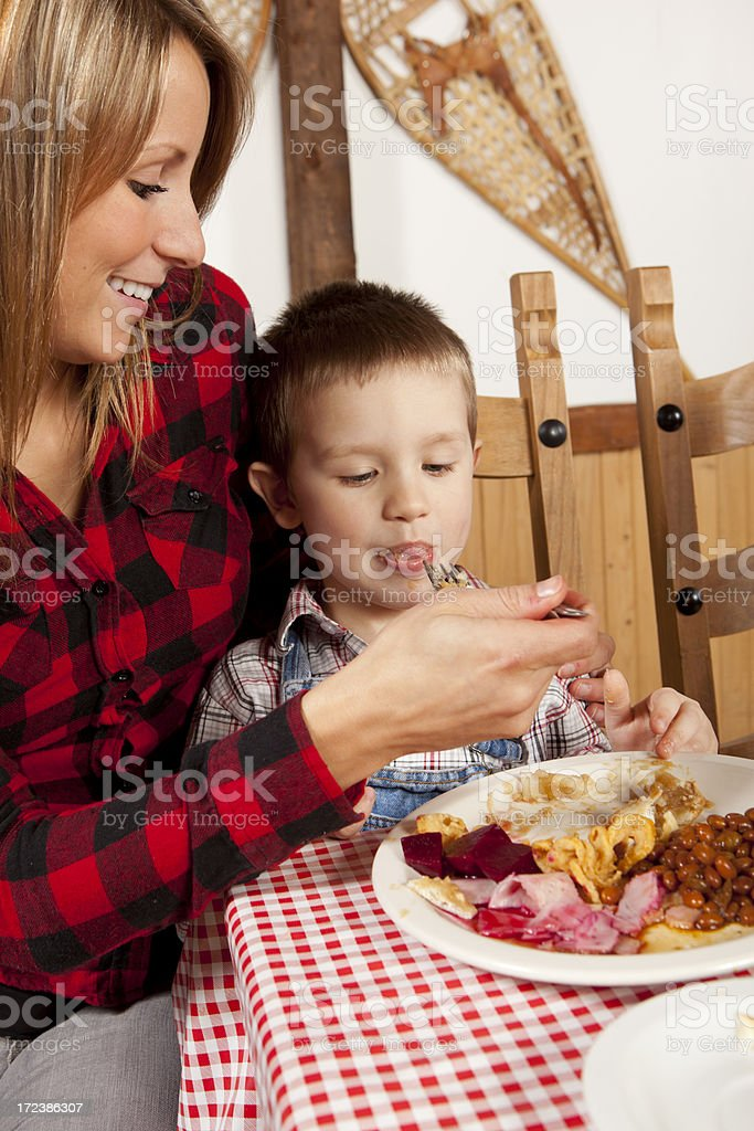Monther give breakfast to his son at sugar shack stock photo