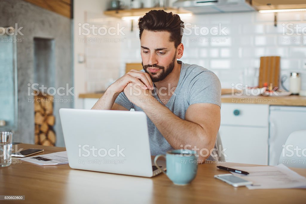 Young man worried about his finances at home. He is wearing pajamas...