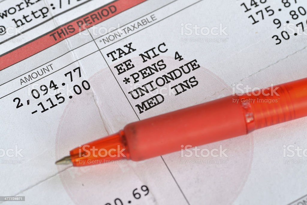 Monthly pay slip and red pen. stock photo