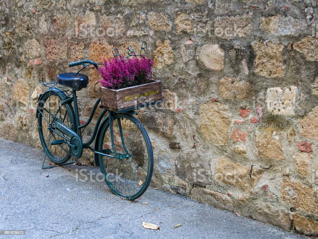 Montichiello - Italy, October 29, 2016: A beautiful bicycle with flowers in a quiet street in Montichiello, Tuscany stock photo