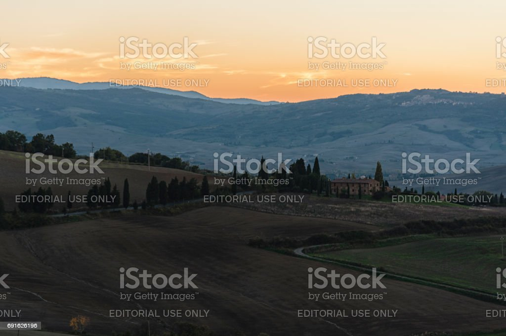 Montichiello - Tuscany/Italy: October 29, 2017: Winding Cypress lined road in Monticchiello, Val d'Orcia Tuscany Italy at sunset stock photo
