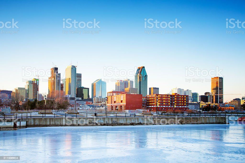 Montreal skyline above frozen canal at sunset stock photo