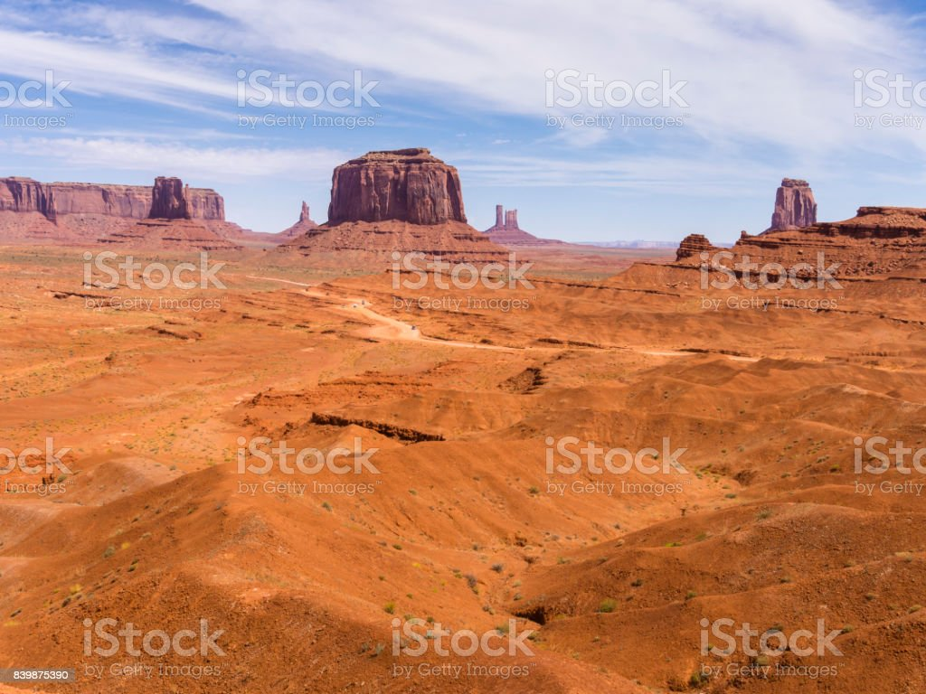 A dirt road is winding through Butte rock formations at Monument...