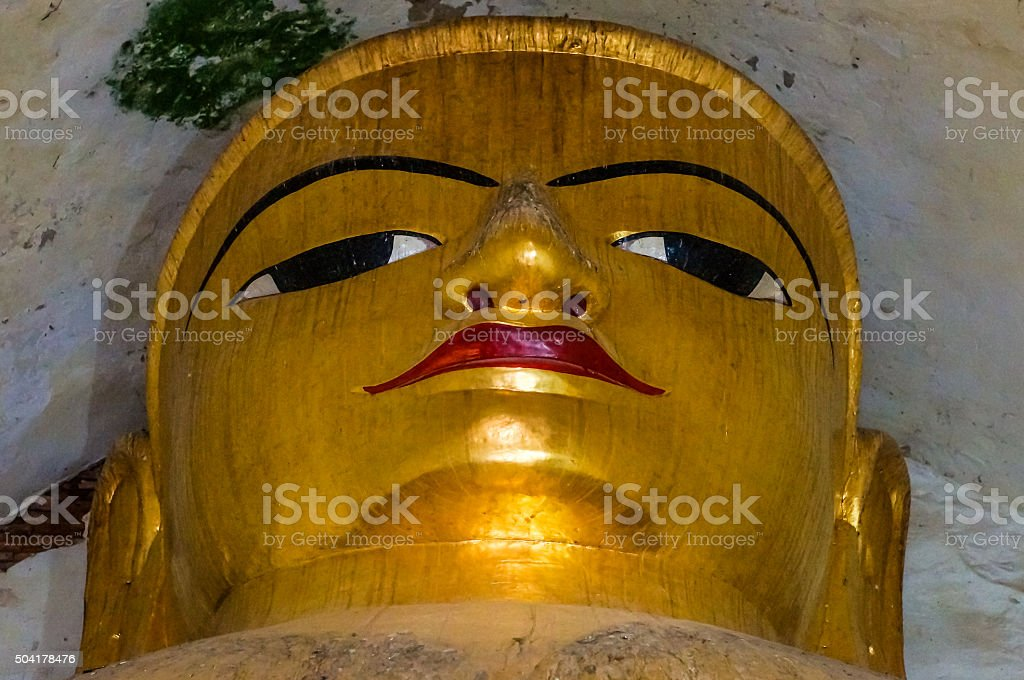 Monumental golden Buddha Face Portrait in old Temple stock photo