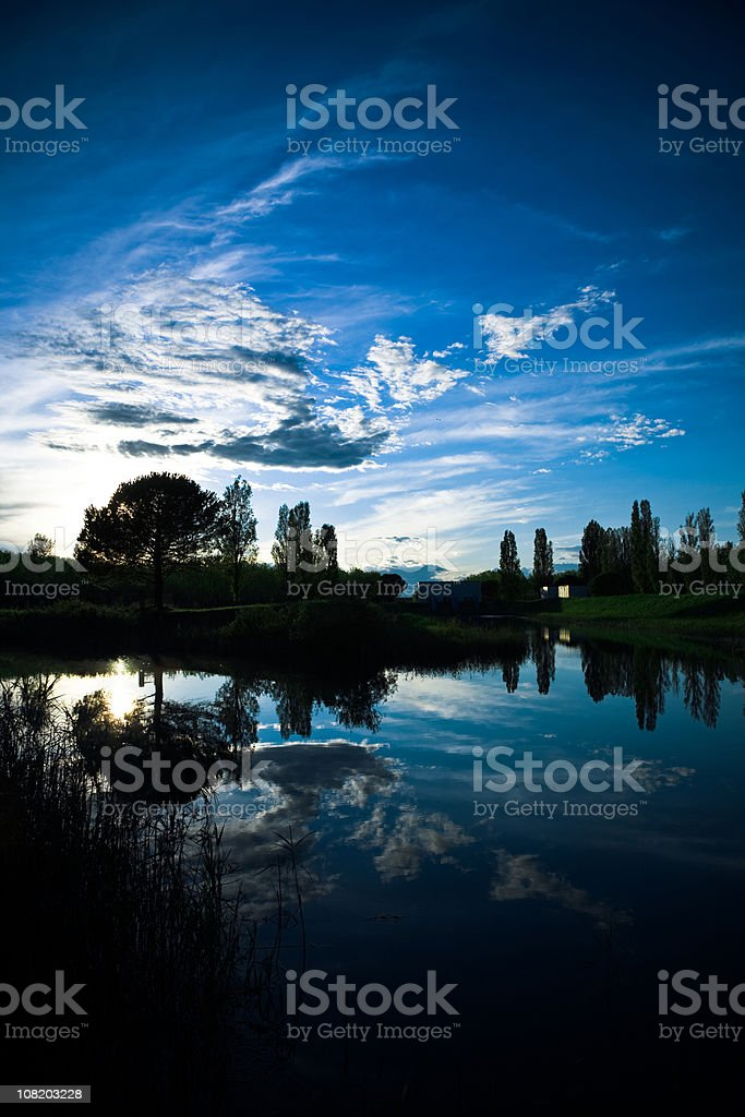 Moody, Dramatic Sky and Sunset Reflection Over Water royalty-free stock photo