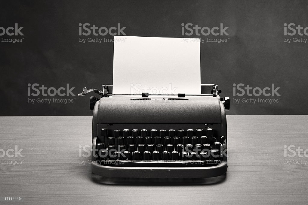 Moody film noir shot of vintage typewriter and blank paper stock photo