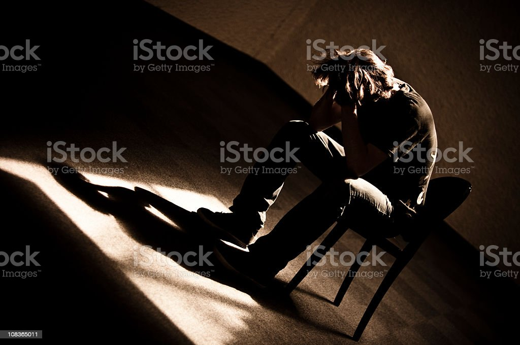 Moody monotone shot of a depressed person slumped in chair stock photo