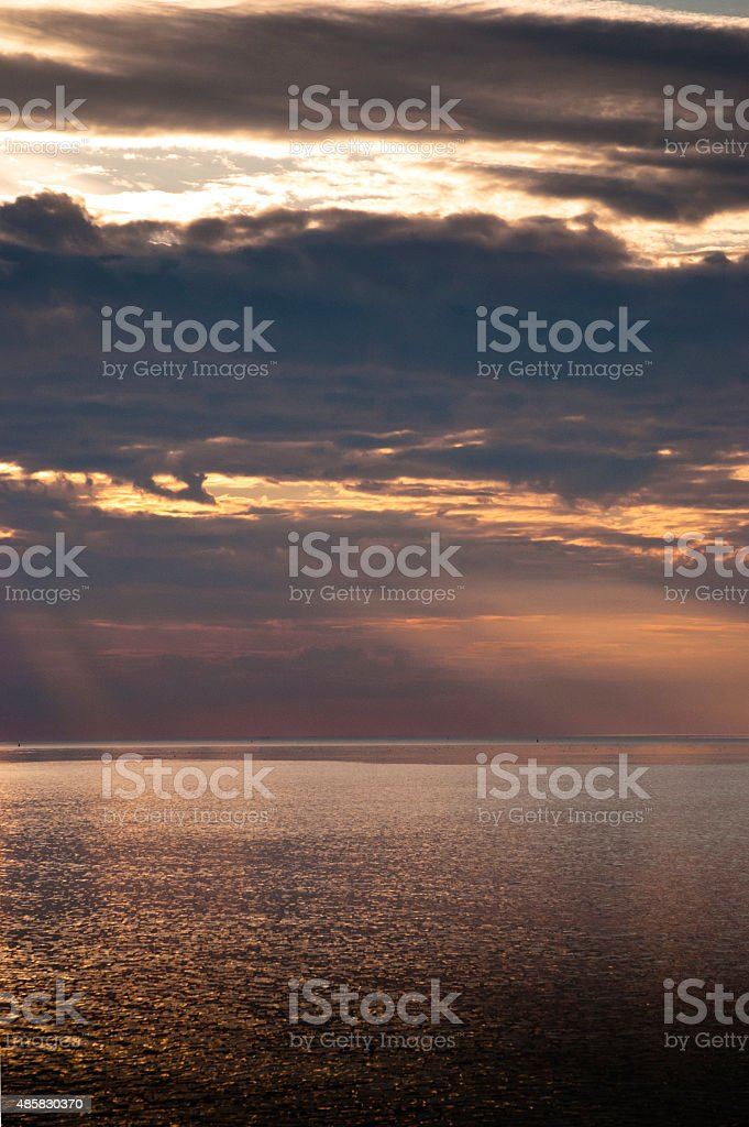 Moody Northsea sky reflection in Northsea water at dusk stock photo