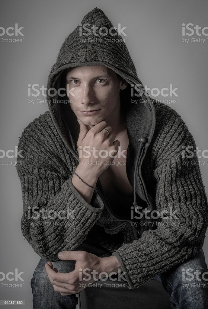 Moody shot of young man in hoodie contemplating stock photo