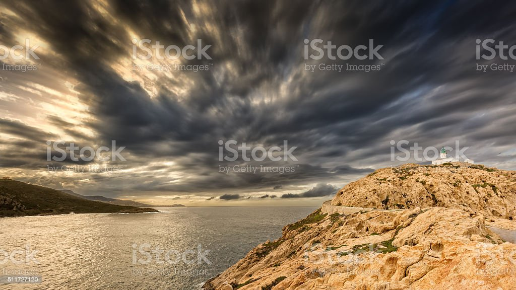 Moody skies over the lighthouse at Ile Rousse in Corsica stock photo