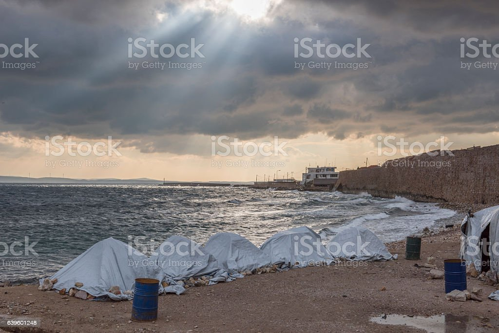 Moody sky and divine light over Greek refugee camp stock photo