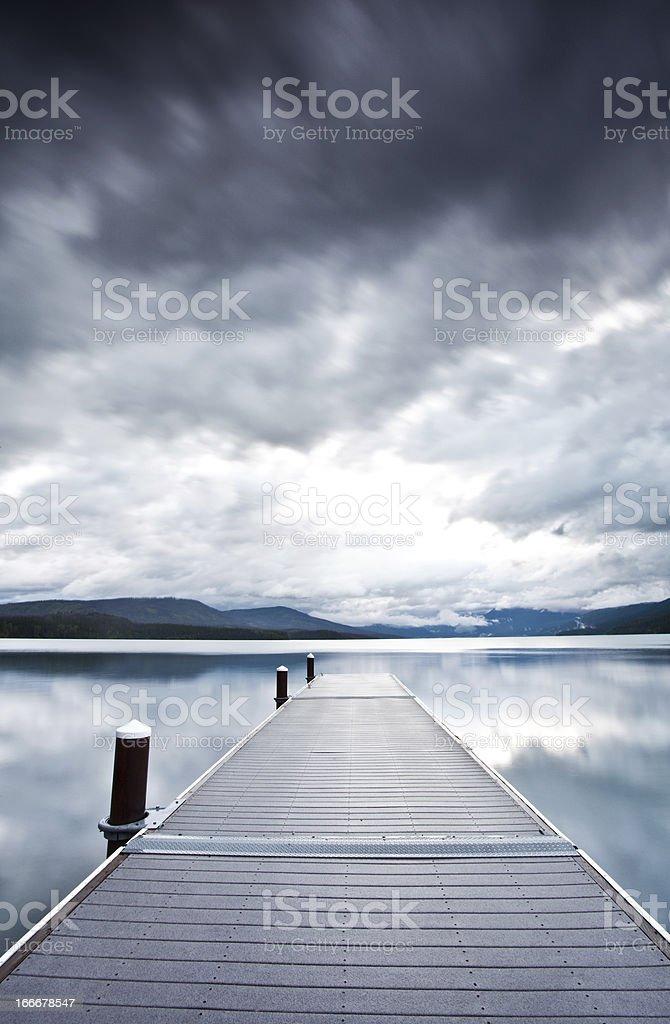 Moody Sky and Dock on Mountain Lake stock photo