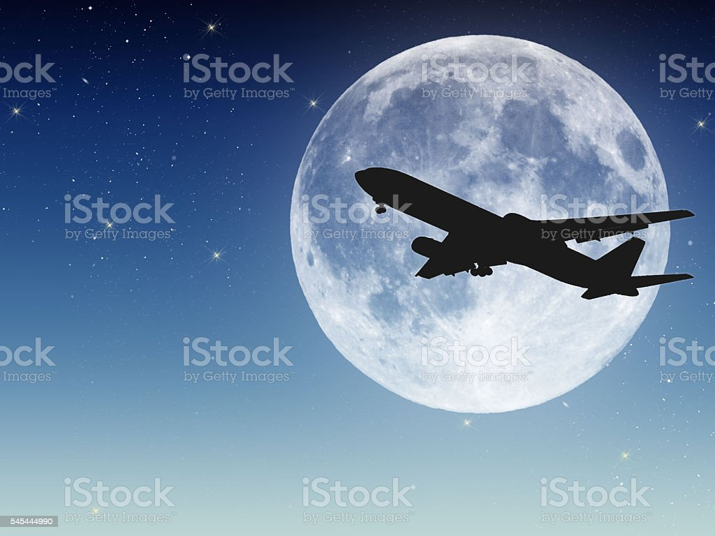 Moon and airplane in the sky of early night stock photo