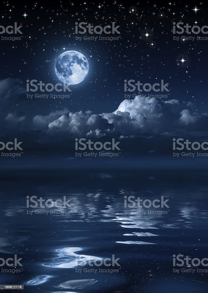 moon and clouds in the night on sea stock photo