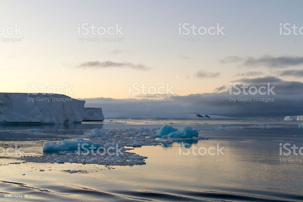 Moon in sky over tabular icebergs, Antarctic Sound stock photo