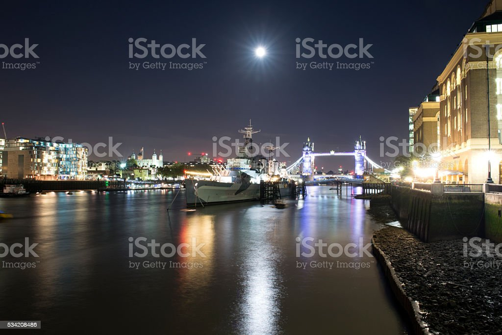 Moon over HMS Belfast, River Thames at night stock photo