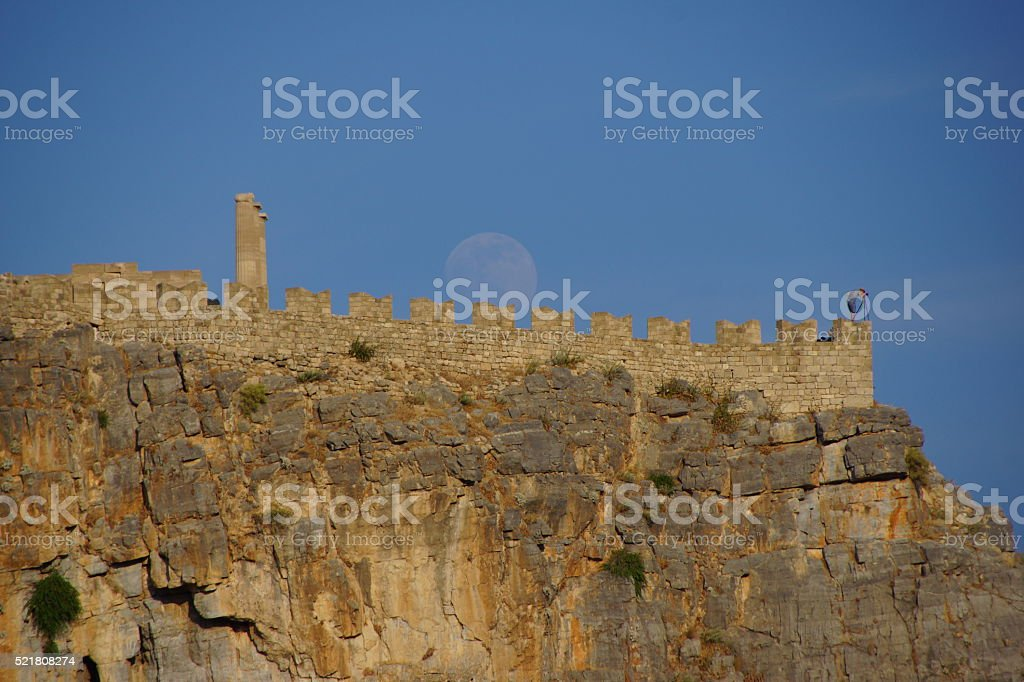 Moon over Lindos fortress, Rhodes. stock photo
