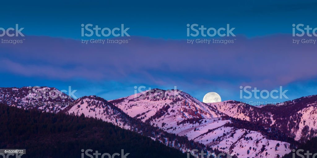 Moon rise over mountains with alpen glow pink light stock photo