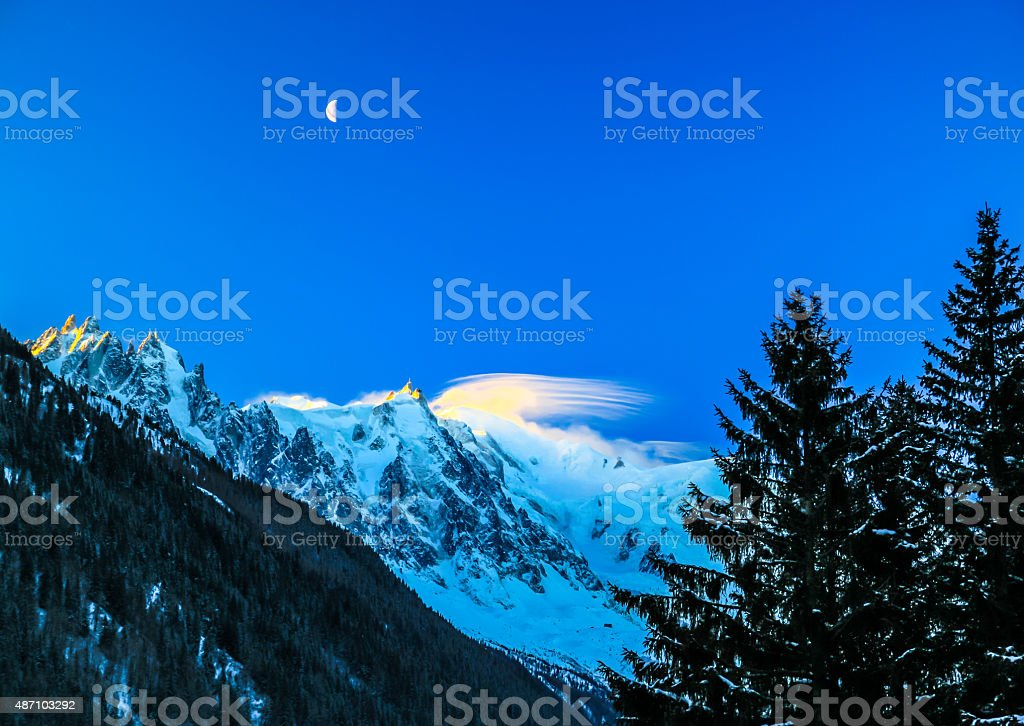 Moon rises above the Mount Blanc in France. stock photo