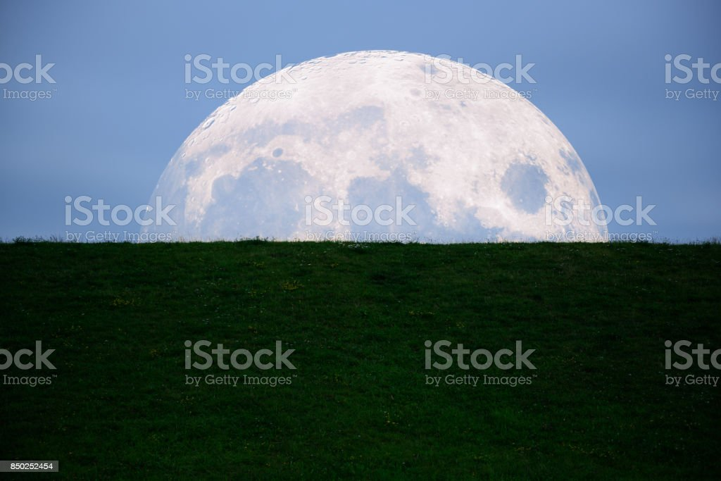 Moon setting against grass bank stock photo