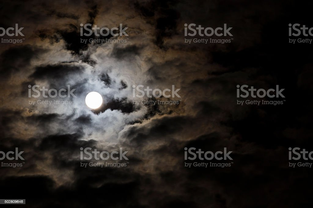 Moon shining through the clouds stock photo