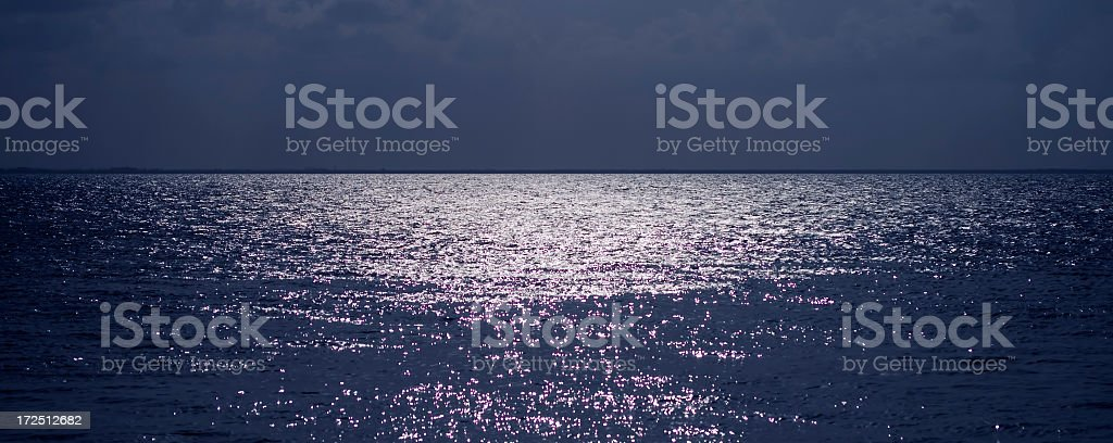 Moonlight on flat horizon view of the ocean with ripples royalty-free stock photo