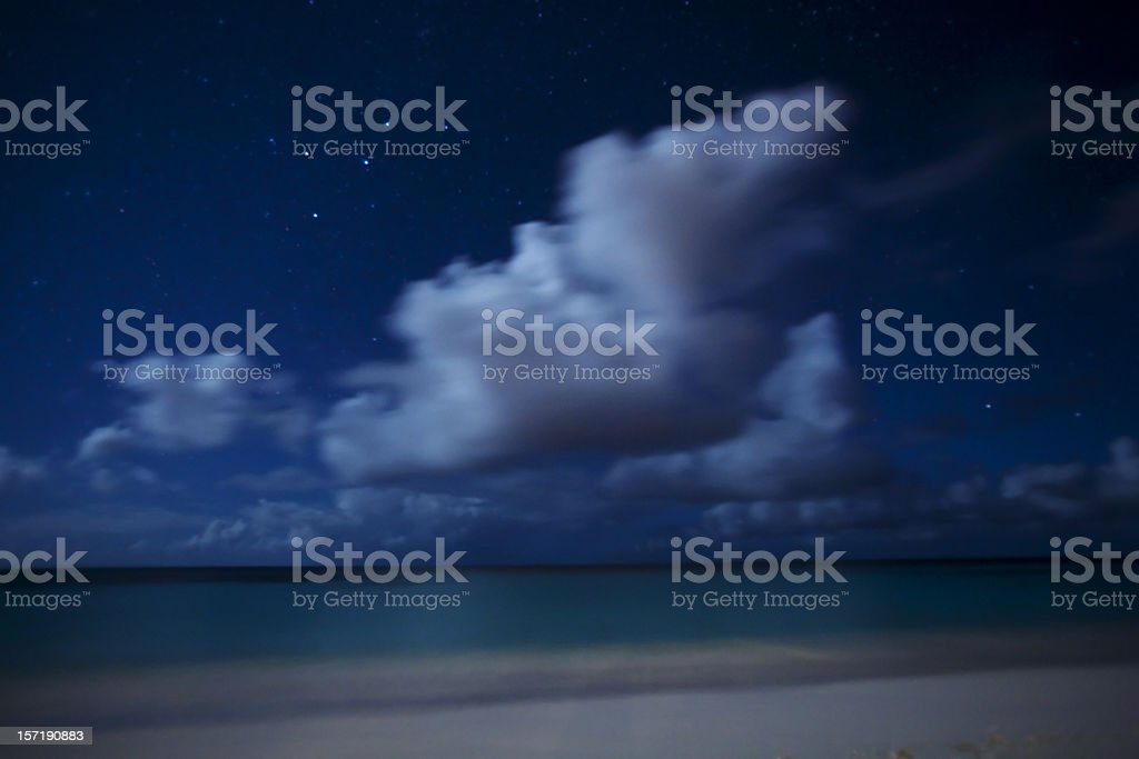 Moonlit clouds, beach and stars stock photo