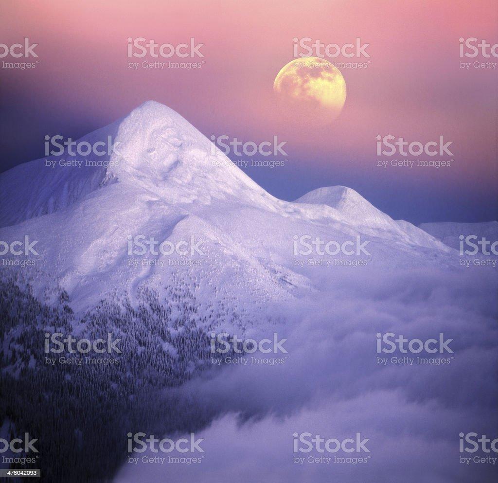 Moonrise among alpine peaks stock photo