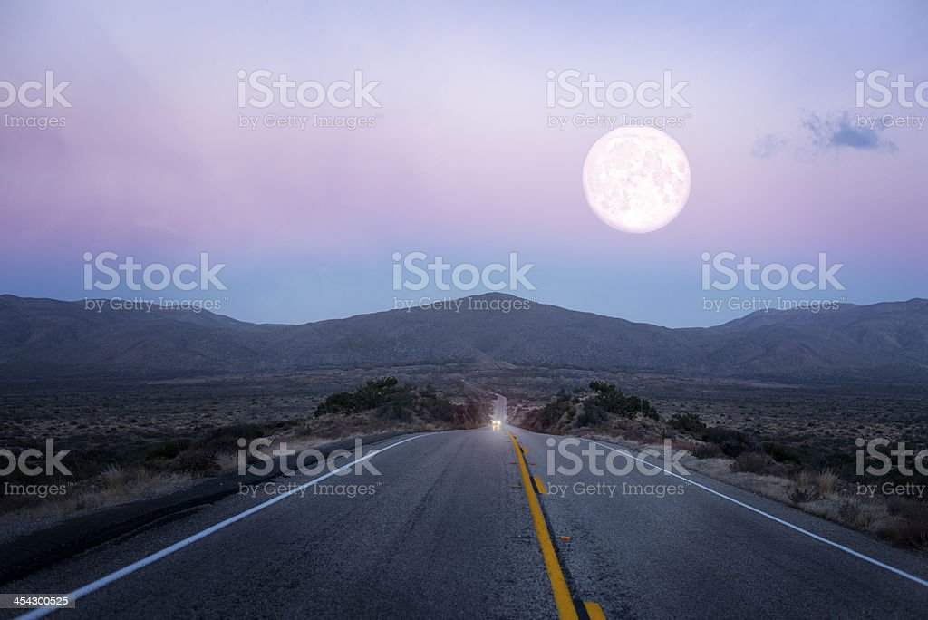 Moonrise over the lonely desert road stock photo