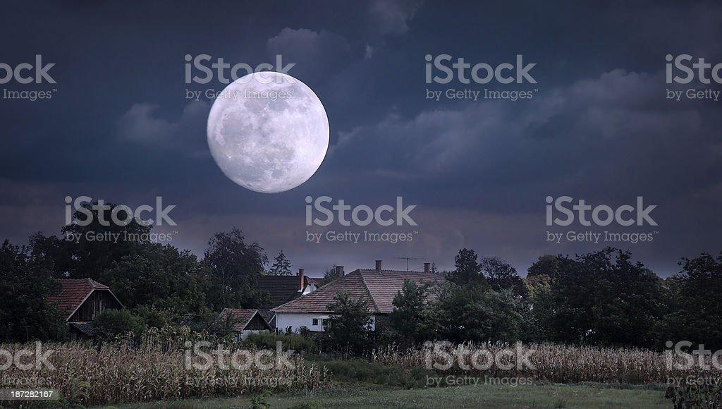 Moonrise over village stock photo