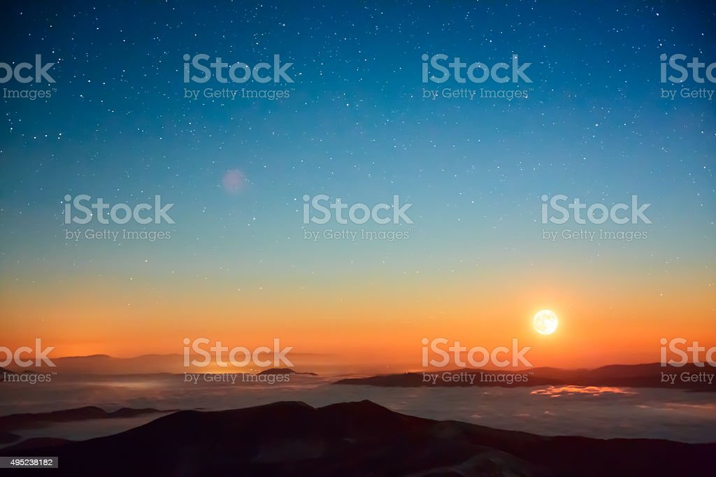 Moonset in cloudy mountains stock photo