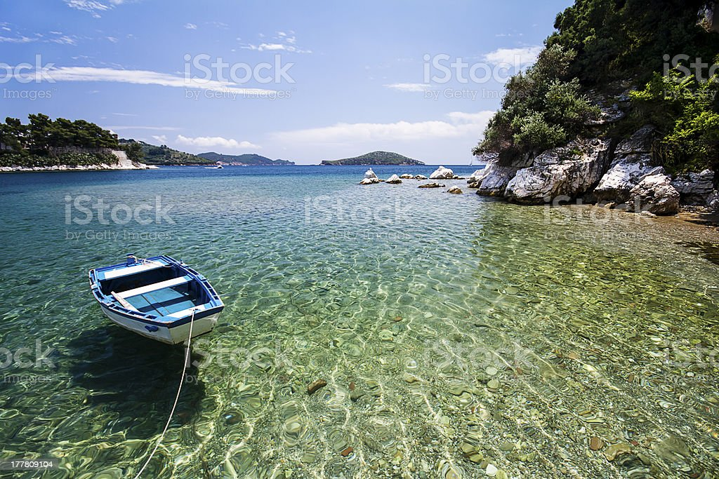 Moored boat near the beautiful cove, clear water. royalty-free stock photo