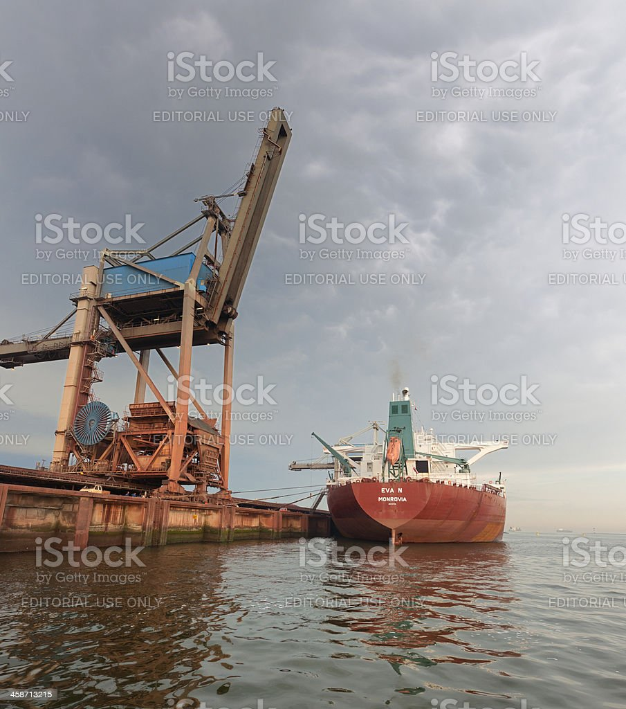 moored cargo ship in harbor at dawn stock photo