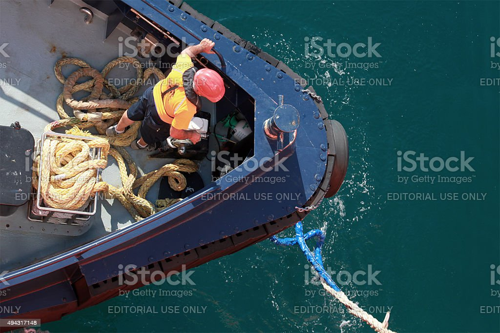 Mooring operations, man at work with rope stock photo