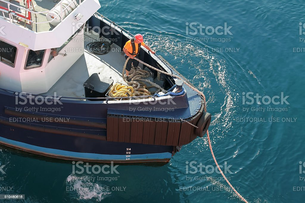 Mooring operations, man at work with ropes stock photo