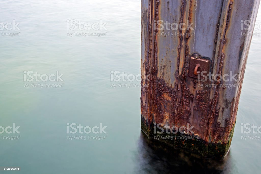 mooring pole from rusty metal in the sea, long exposure stock photo