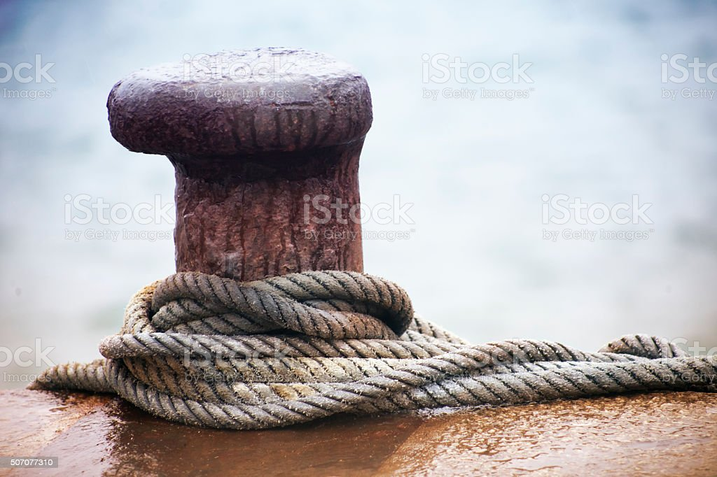 Mooring post and thick ropes, sea background. stock photo