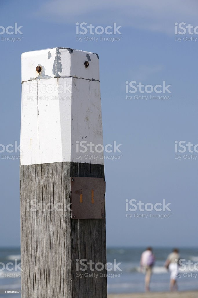 mooring post and two walking people on a beach stock photo