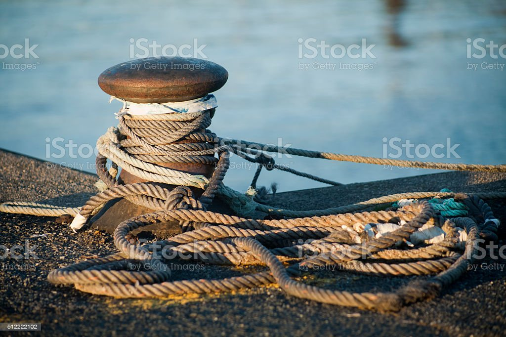 Mooring post in evening sunlight. stock photo