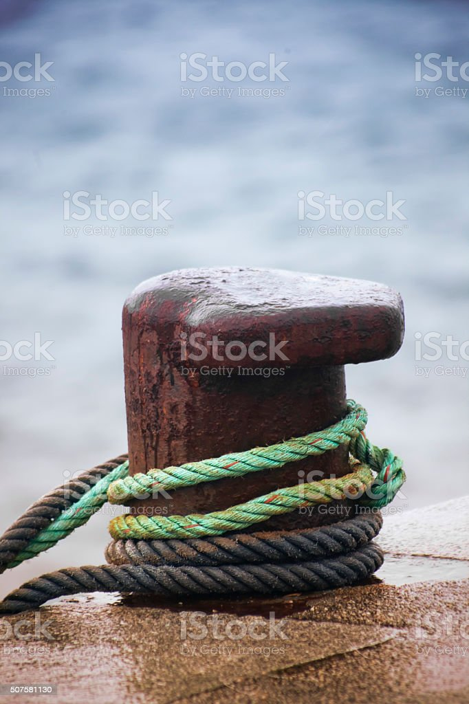 Mooring post on stone dock,thick ropes and sea background. stock photo