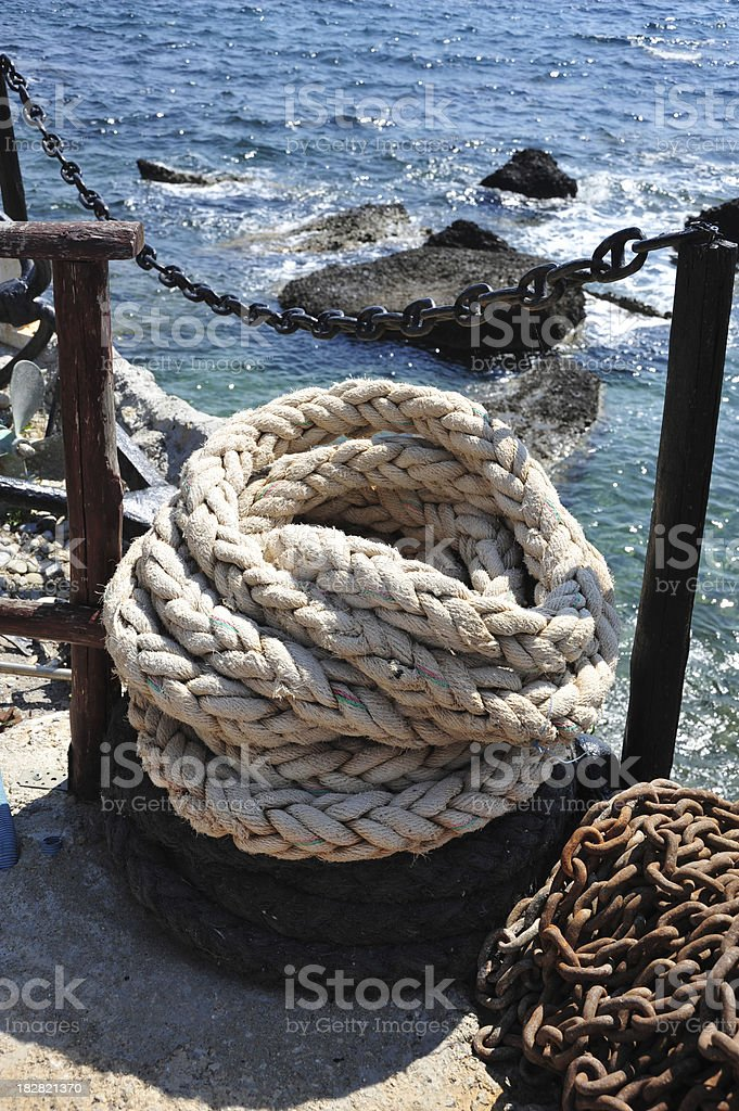 Mooring rope and chain on the harbour wall stock photo