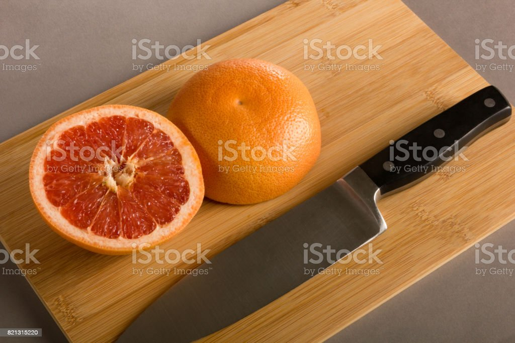 More Approachable Yet Still Ominous Knife and Grapefruit on Cutting Board stock photo