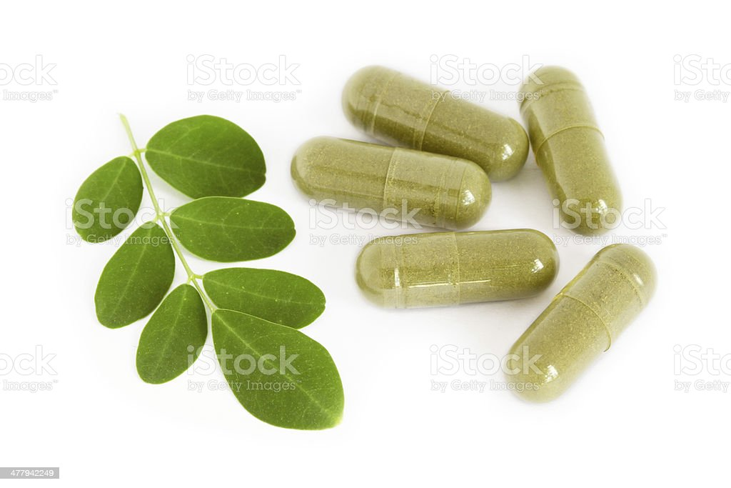 Moringa oleifera capsule with green fresh leaves royalty-free stock photo