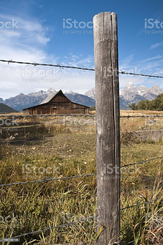 Mormon Barn and Grand Tetons Seen Through Fence stock photo