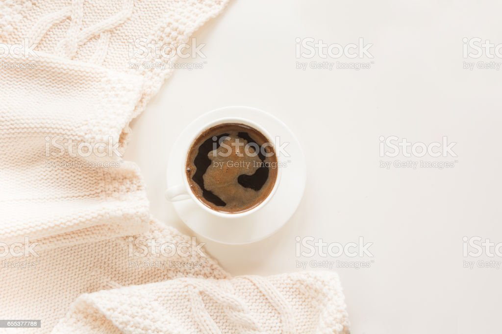 Morning breakfast, a cup of black coffee in the pastel colors with warm gentle scarf on a white background. Top view and copy space. stock photo