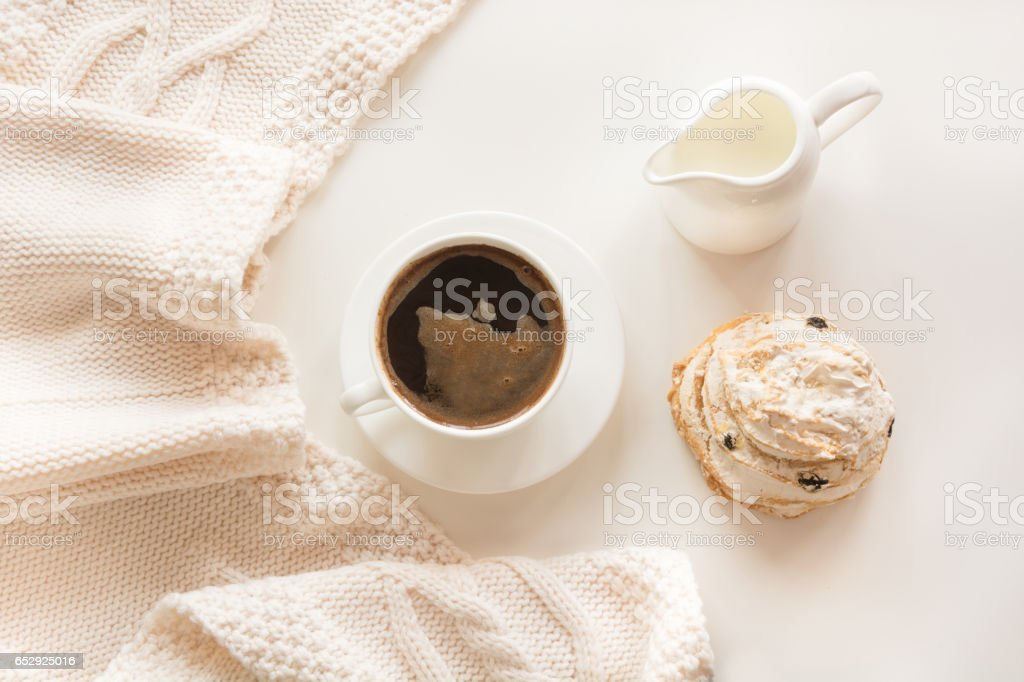 Morning breakfast, a cup of black coffee with milk and pastries in the pastel colors with warm gentle scarf on a white background. Top view. stock photo